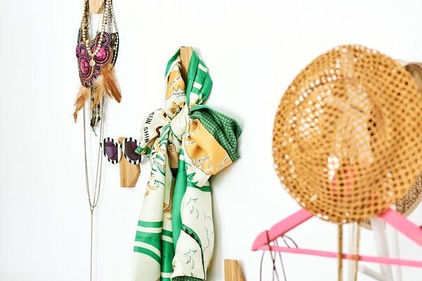 Asymmetrische Bambushaken an der Wand, jeder mit einem anderen Accessoire: Sonnenbrille, Schal, Ketten und ein Hut.