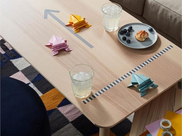 Asztalon színes papírbékák, két pohár limonádé és harapnivaló.