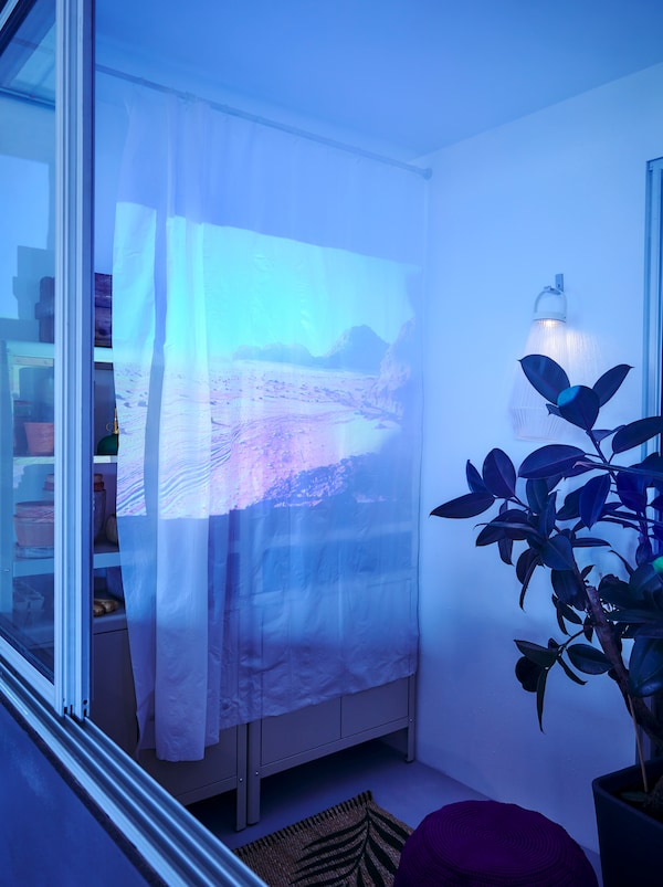 At one end of a balcony, a film is projected on a white BJÄRSEN shower curtain hung as a film screen from a BOTAREN rod.