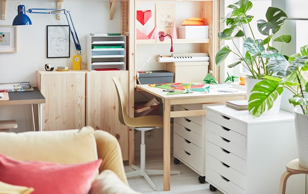 At one end of a wall-wide IVAR storage unit, a workspace created by a folded-out table, covered with coloured paper.