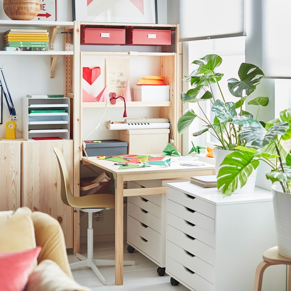 At one end of a wall-wide IVAR storage unit, a workspace created by a folded-out table, covered with colored paper.