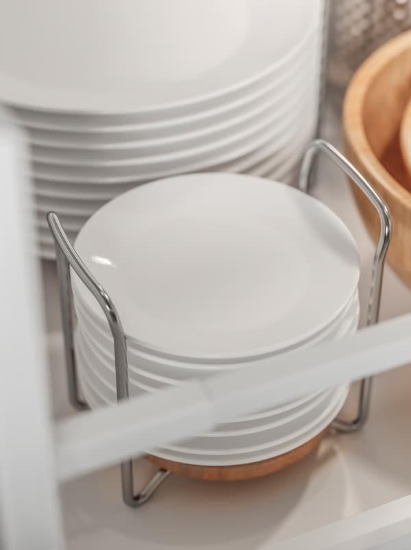 أطباق بيضاء مكدسة فوق بعضها البعض وتحتل مكانها داخل حامل أطباق VARIERA مصنوع من الستنلس ستيل والخشب.