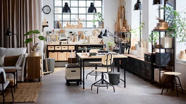 Atelier à domicile de style industriel aux plafonds hauts et aux grandes fenêtres ; meubles en bois et en métal noir.