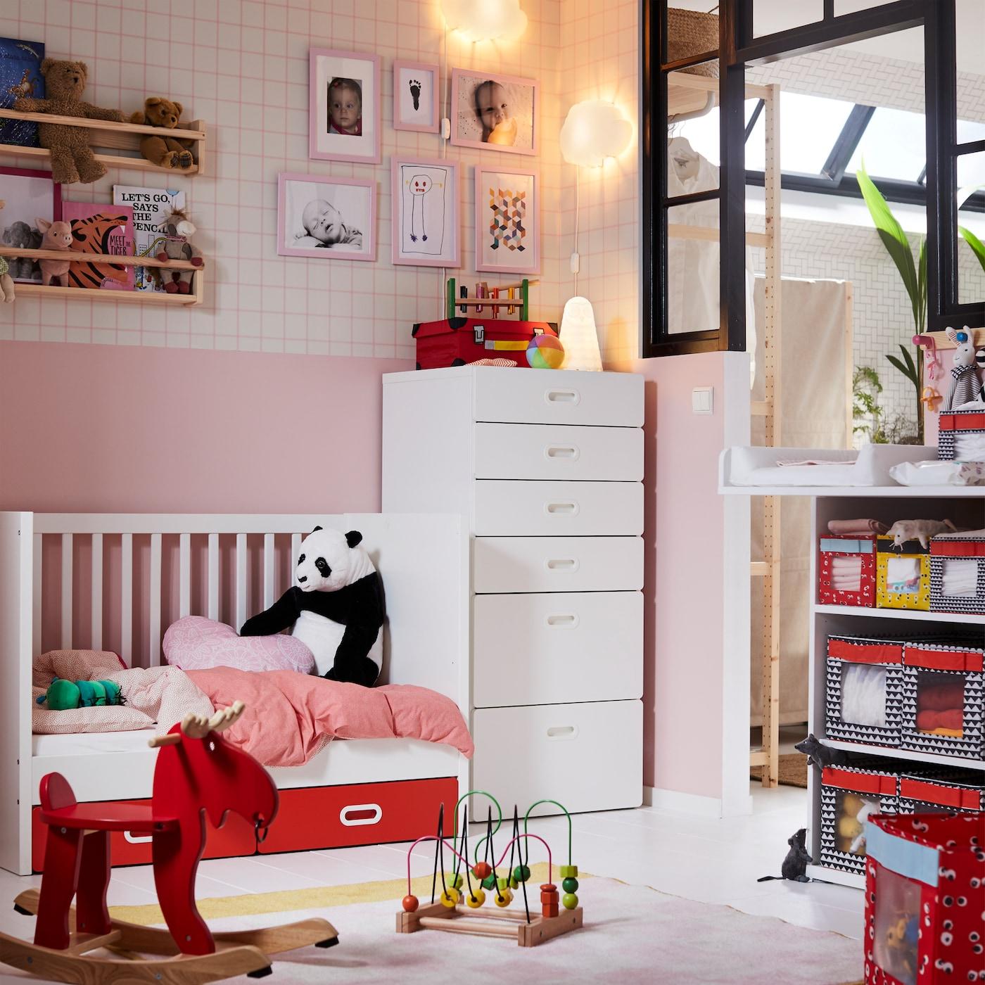 أثاث أطفال رضع أبيض STUVA من ايكيا سرير أطفال ووحدة ذات ستة أدراج في غرفة أطفال رضع وردي بها ألعاب ودب طري.