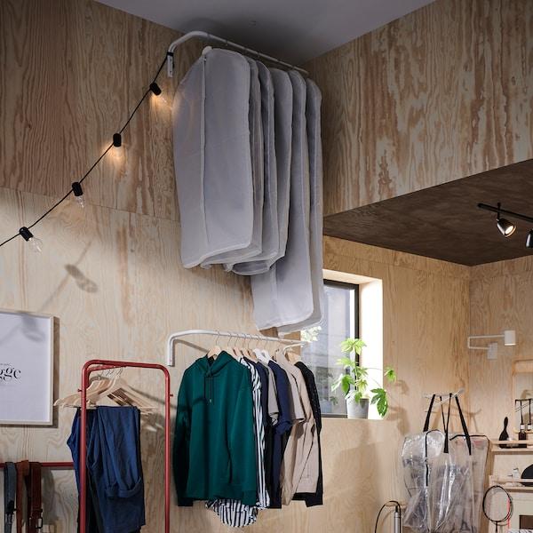 اثنان من أعمدة تعليق الملابس مثبتة على الحائط. إحداهما على السقف وعليه ملابس في أغطية ملابس، والآخر على ارتفاع أقل في متناول اليد.