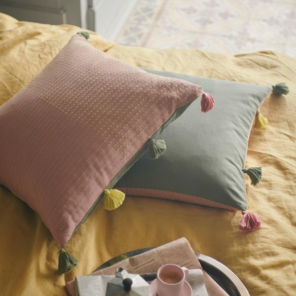اثنان من أغطية الوسائد KLARAFINA حيث تظهر الجوانب الوردية والخضراء لهما مع شرابات ملونة على الحافة أيضًا.