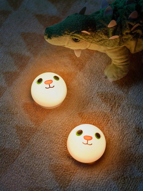اثنان من الأضواء الليليةKORNSNÖ على سجادة أطفال مزركشة زاهية، وديناصورJÄTTELIK في الخلفية.
