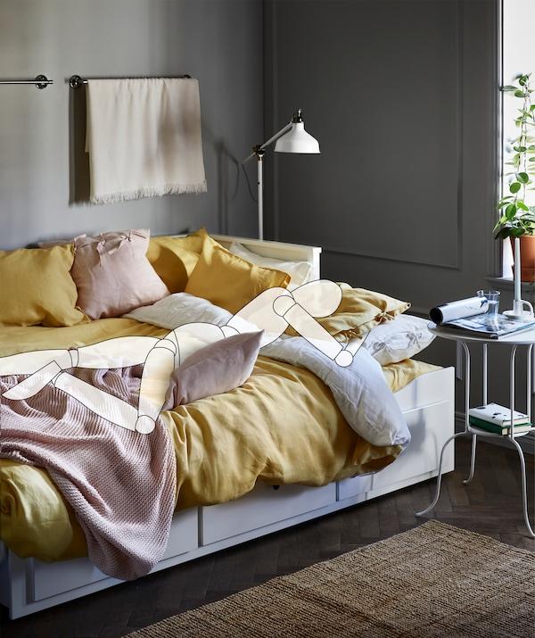 Auf dem Bauch liegend ist die Zeichnung einer Person auf einem Bett zu sehen. Sie hält ein Kissen im Arm, u. a. mit einem AINA Kissenbezug in Hellrosa.