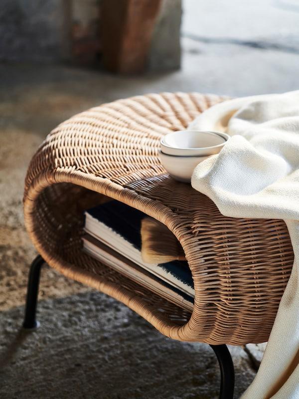 Auf einem GAMLEHULT Hocker mit Aufbewahrung liegt eine weiße Decke neben einer weißen Schüssel. Im Hocker liegen Bücher.