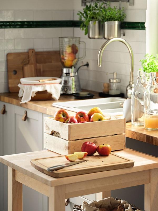 Auf einem Rollwagen aus Holz werden auf einem Schneidebrett Äpfel geschnitten und als Saft in Glasflaschen mit Verschluss gefüllt.