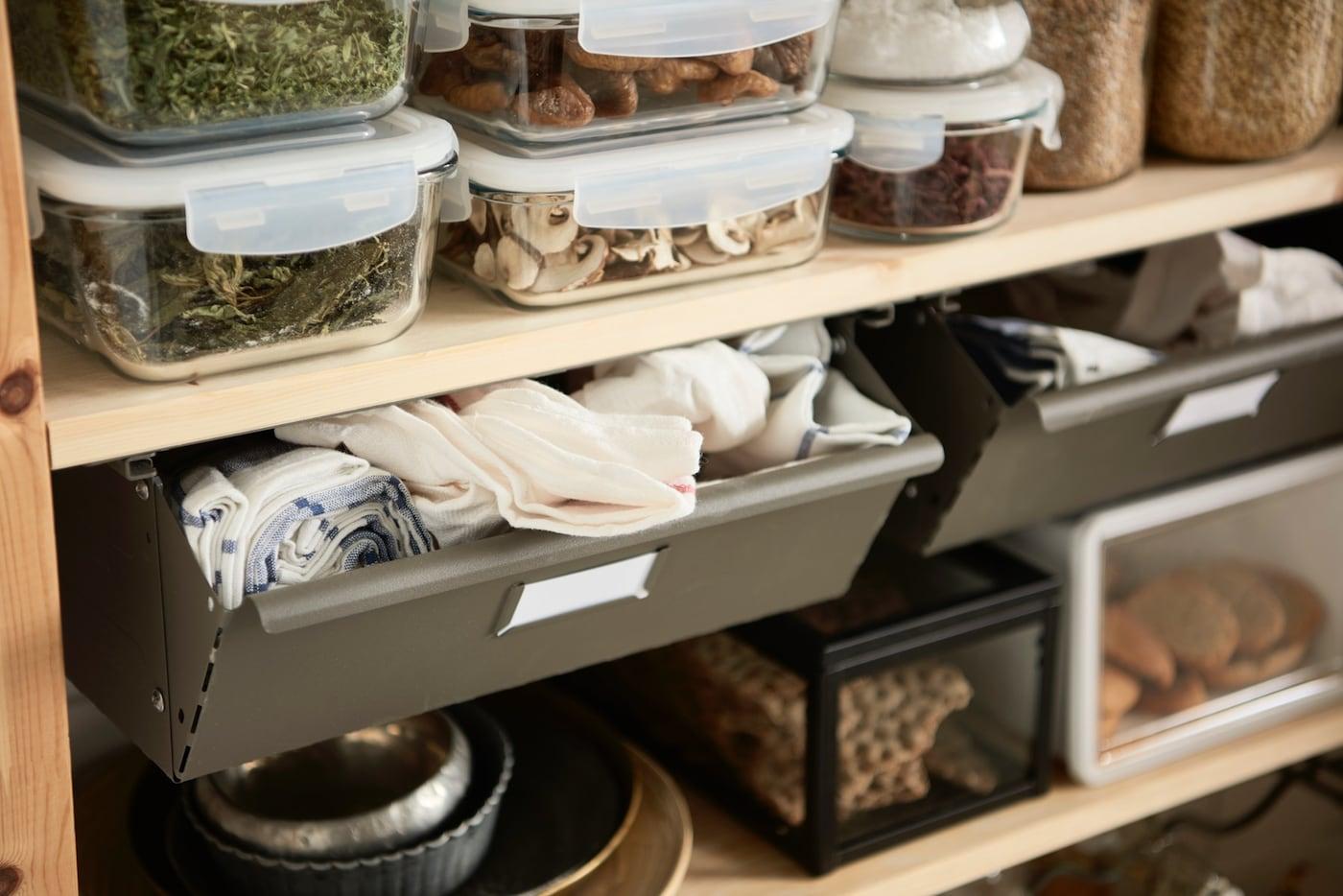 Aufbewahrung von Lebensmitteln, Küchentextilien und Geschirr in einem offenen Regal.