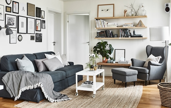 Aufnahme eines Wohnzimmers in neutralen Farben, darin sind ein graues Sofa, graue Sessel, gerahmte Bilder & Regale zu sehen.
