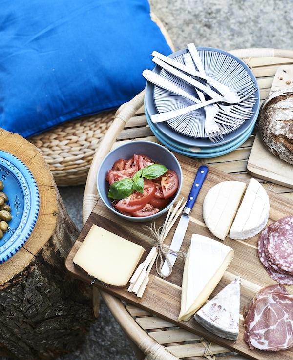 Aufschnitte, Käse und blaues Geschirr auf SMÅÄTA Schneidebrett Akazie auf einem Couchtisch