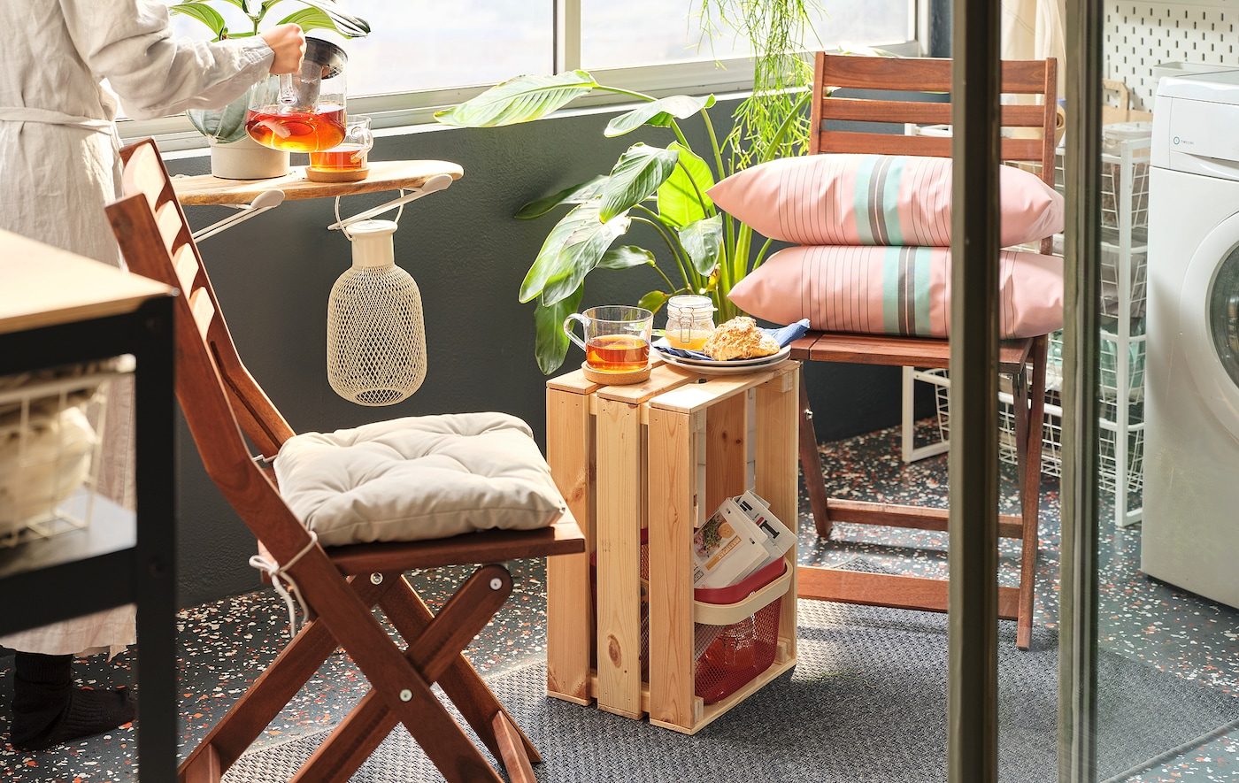 Auringonvalossa kylpevä parvekkeen nurkka, joka muodostuu taittotuoleista ja KNAGGLIG laatikosta, joka on asetettu kyljelleen pieneksi sivupöydäksi tuolien välissä.