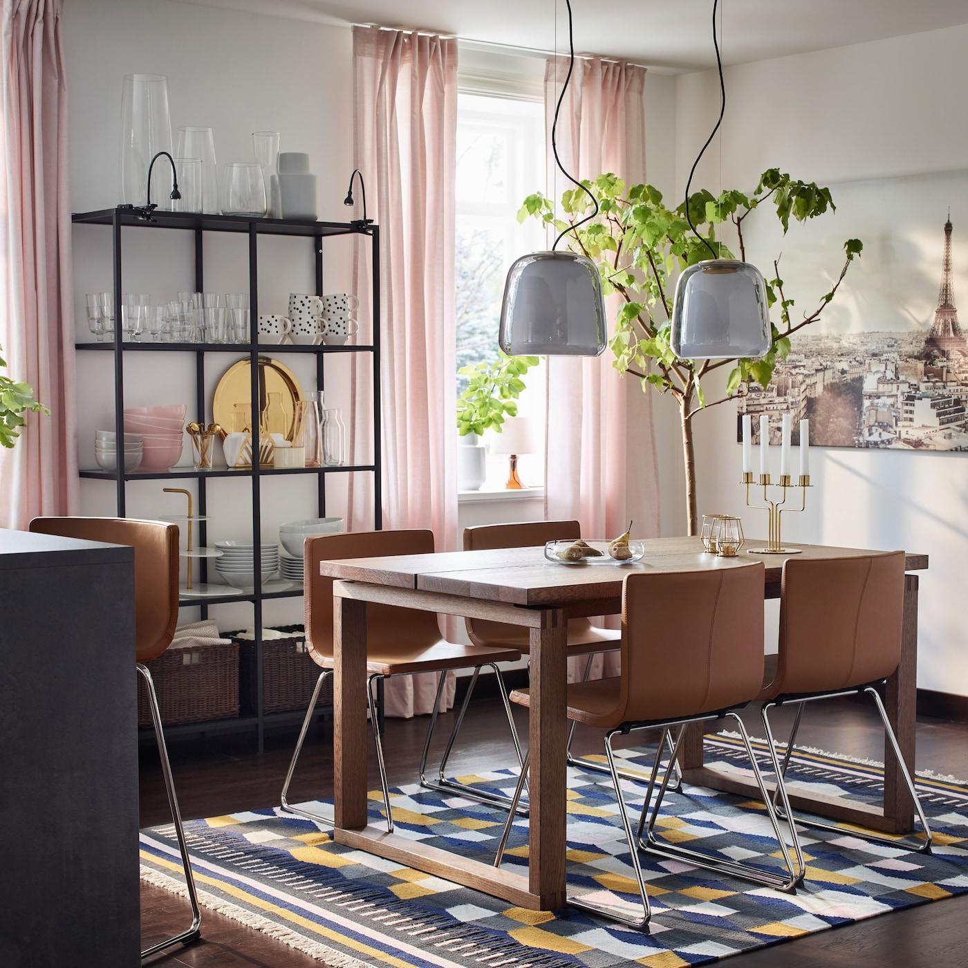 Avec leurs arêtes et leurs lignes droites, la table de salle à manger brune IKEA MÖRBYLÅNGA en placage de chêne et les chaises BERNHARD brun doré forment un duo moderne.