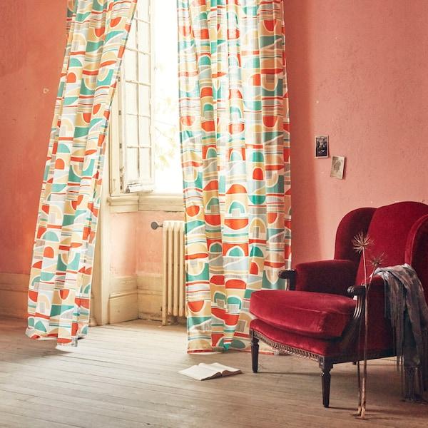 Avoimessa ikkunassa moniväriset, graafisesti kuvioidut MARTORN-verhot liehuvat tuulessa. Vieressä punainen, samettinen nojatuoli.