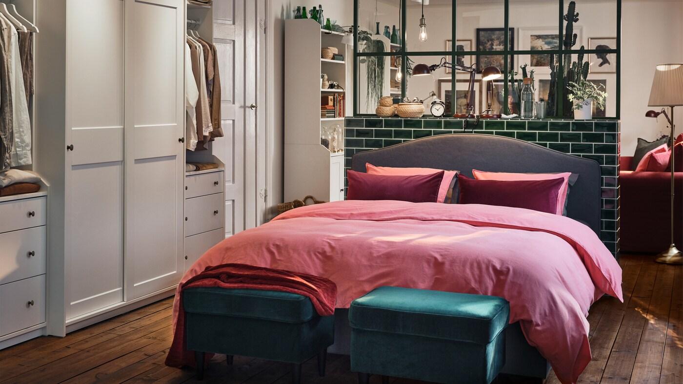 Avoin huone, jossa vaaleanpunaisilla petivaatteilla peitelty HAUGA-sänky. Sängyn edessä kaksi vihreää rahia.