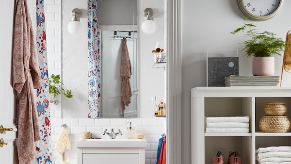 Avoin kylpyhuoneen ovi, ripustimessa roikkuu kylpytakki ja sisäpuolella valkoinen allaskaluste, peili ja molemmin puolin seinävalaisimet.