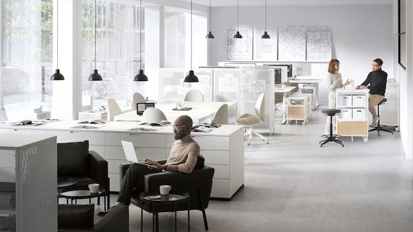 Avoin toimistotila, jossa kaksi taukopaikkaa. Mies työskentelee KOARP-lepotuolissa ja kaksi henkilöä keskustelee BEKANT-hyllykön äärellä.