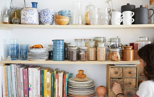 أواني مطبخ، وكتب ومرطبانات بها مكونات جافة على ثلاثة رفوف خشبية.