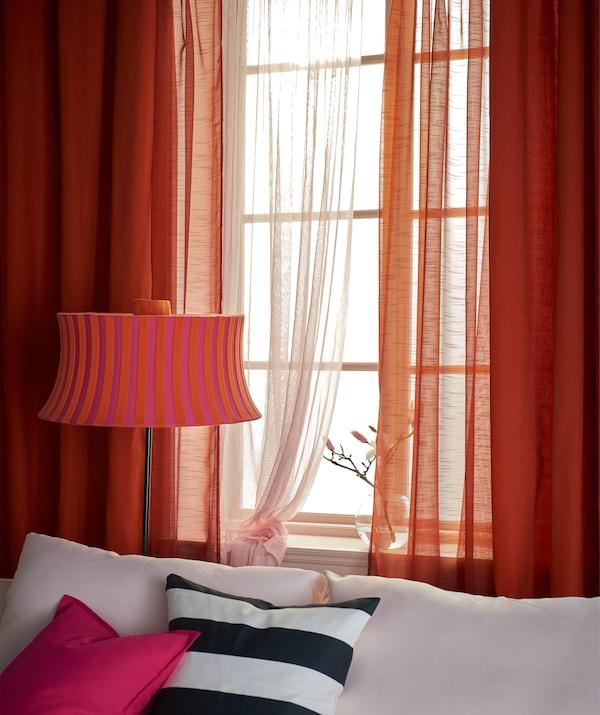 ايكيا لديها الكثير من ستائر غرف الجلوس مثل ستائر MARIAM السميكة باللون البرتقالي. إنها توفر لك إمكانية إظلام الغرفة والحصول على الخصوصية. استخدمنا طبقات الستائر مع وضع الستائر السميكة من أعلى. وبالقرب من النافذة استخدمنا ستائر شفافة رودي وبرتقالي تتيح دخول الضوء.