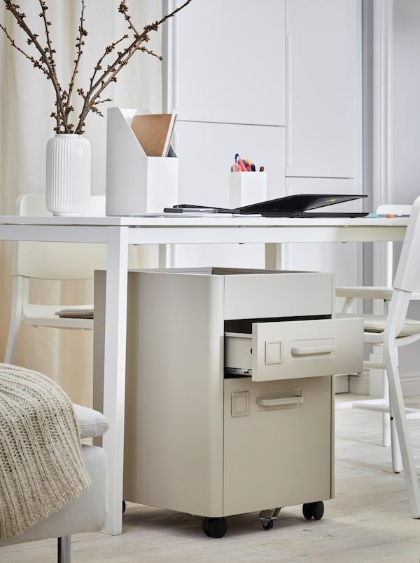 Az ágy mellett egy fehér asztal áll, rajta irodai kellékek, alatta egy IDÅSEN fiókos elem.