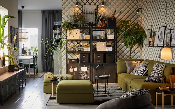 A black shelving unit against a diamond patterned black and white wall with a green sofa set in front.