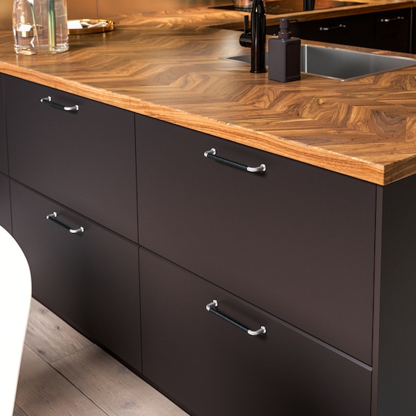 Kitchen doors in anthracite, handles in black leather and stainless steel, and a worktop in walnut.