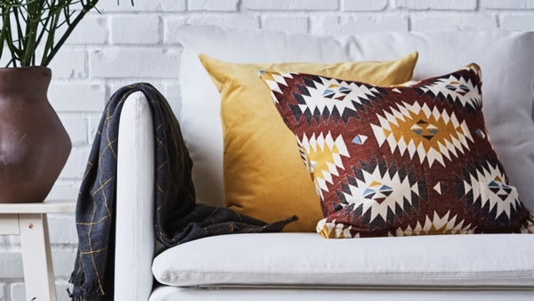 A multicolored red cushion in front of a yellow cushion on a white sofa