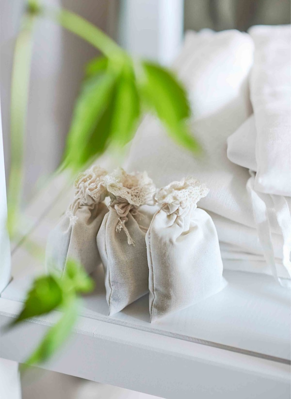 Three small fabric bags of lavender lean against white sheets.