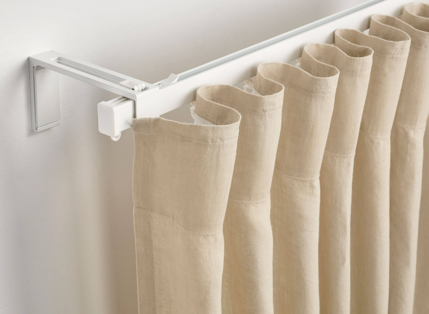 Close-up of a curtain rod with gray curtains hanging from it.