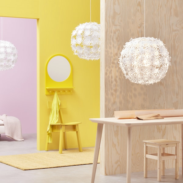 Multi-coloured room with GRIMSÅS pendant lamps, a table and stools.