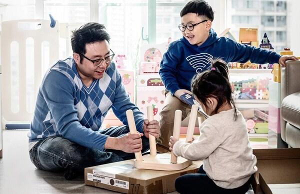 Un padre che monta uno sgabello IKEA in soggiorno insieme ai due figli.