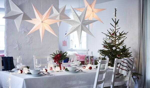 Ein gedeckter Weihnachtstisch mit einem Tannenbaum und leuchtenden Sternen über dem Tisch.
