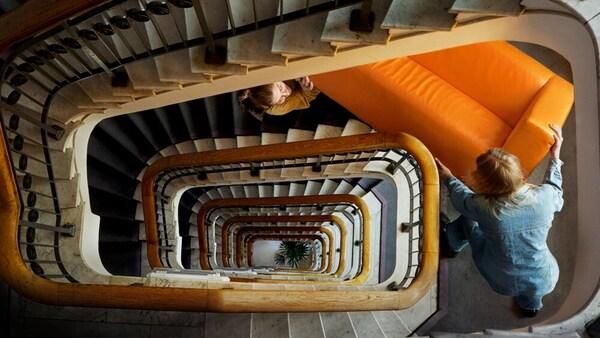 Escadas de um prédio em caracol e duas pessoas a carregar um sofá cor de laranja.