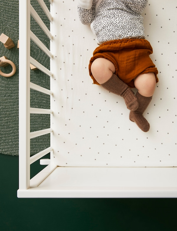Baby lying in a cot with LENAST fitted sheet dressed in cute clothes with wooden toys on a rug on the floor nearby.