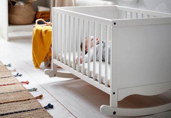 Baby lying in an IKEA SOLGUL crib in a room with white wooden floorboards and natural textile rug and basket.