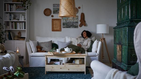 담요가 덮인 거실의 화이트 BACKSÄLEN 박셀렌 소파에서 차 한 잔을 들고 앉아 있는 여성.
