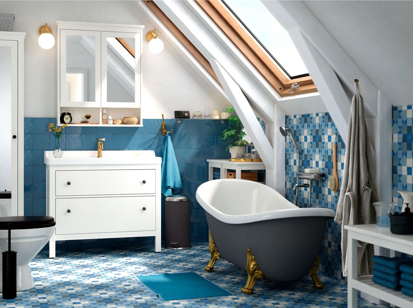 Bad mit blauen Fliesen, weißen Badmöbeln, grauer Wellness-Badewanne & blauem Teppich.