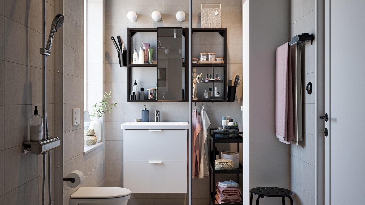 Badeværelse med badeværelsesmøbler i sort og hvid, et forkromet brusesæt, lyserøde håndklæder og en brusebadsdør af glas.