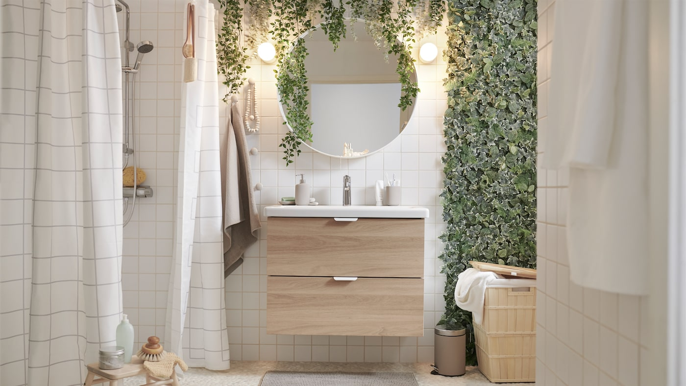 Badeværelse med et brusebad, FEJKA kunstige planter, et ENHET/TVÄLLEN skab med vask, en VILTO taburet af birk og et rundt spejl.