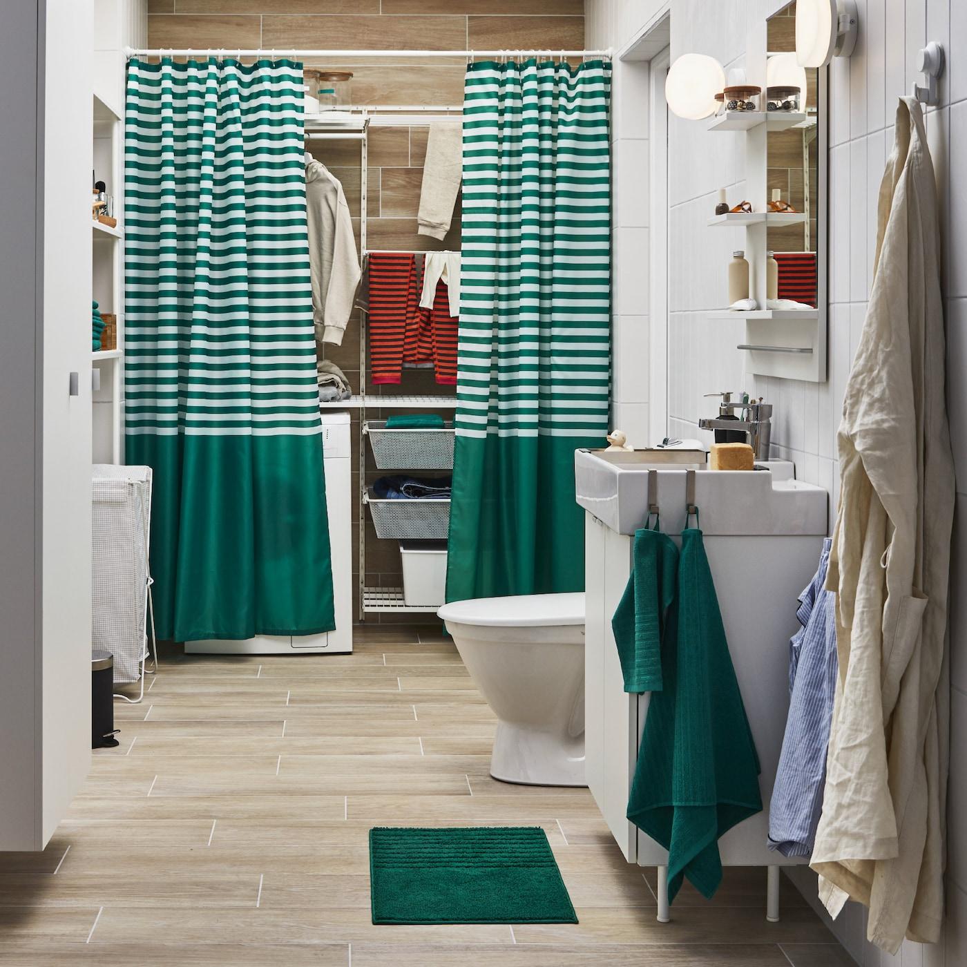 Badeværelse med et vasketøjsområde, der er delvis skjult bag stribede badeforhæng, et hvidt skab med vask og grønne håndklæder.