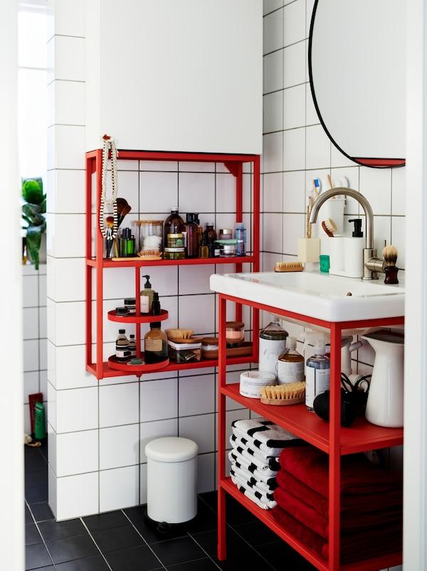 Badeværelse med hvide fliser indrettet med et miks af røde og hvide ENHET moduler med pynteting og tilbehør.