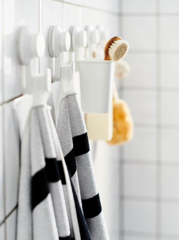Badeværelsesvæg med fliser med en række TISKEN kroge med sugekopper med håndklæder, en skrubbebørste og lignende badeværelsestilbehør.