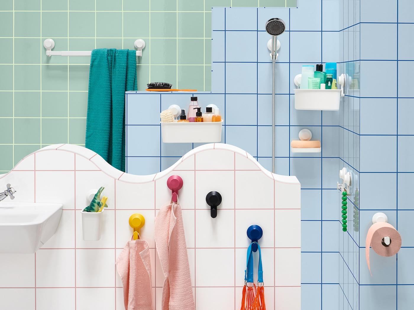 Badezimmer mit blauen, weissen & grünen Fliesen & bunten Saugnäpfen, an denen Badutensilien hängen.