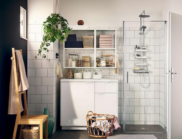 Badezimmer mit weißen Möbeln und einer Dusche mit Gladwänden.