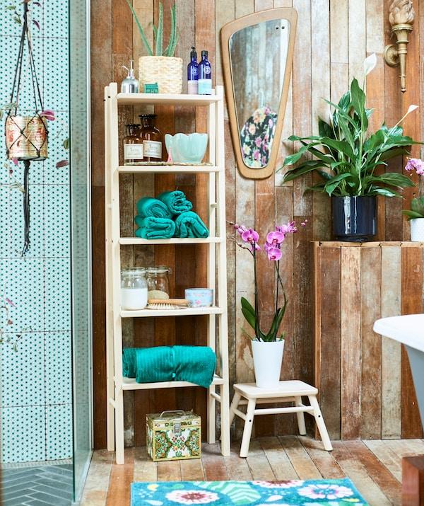 Badkamer in houten spa-stijl en met groenbetegelde inloopdouche, een houten open kast met opgerolde groene handdoeken en potten en planten.