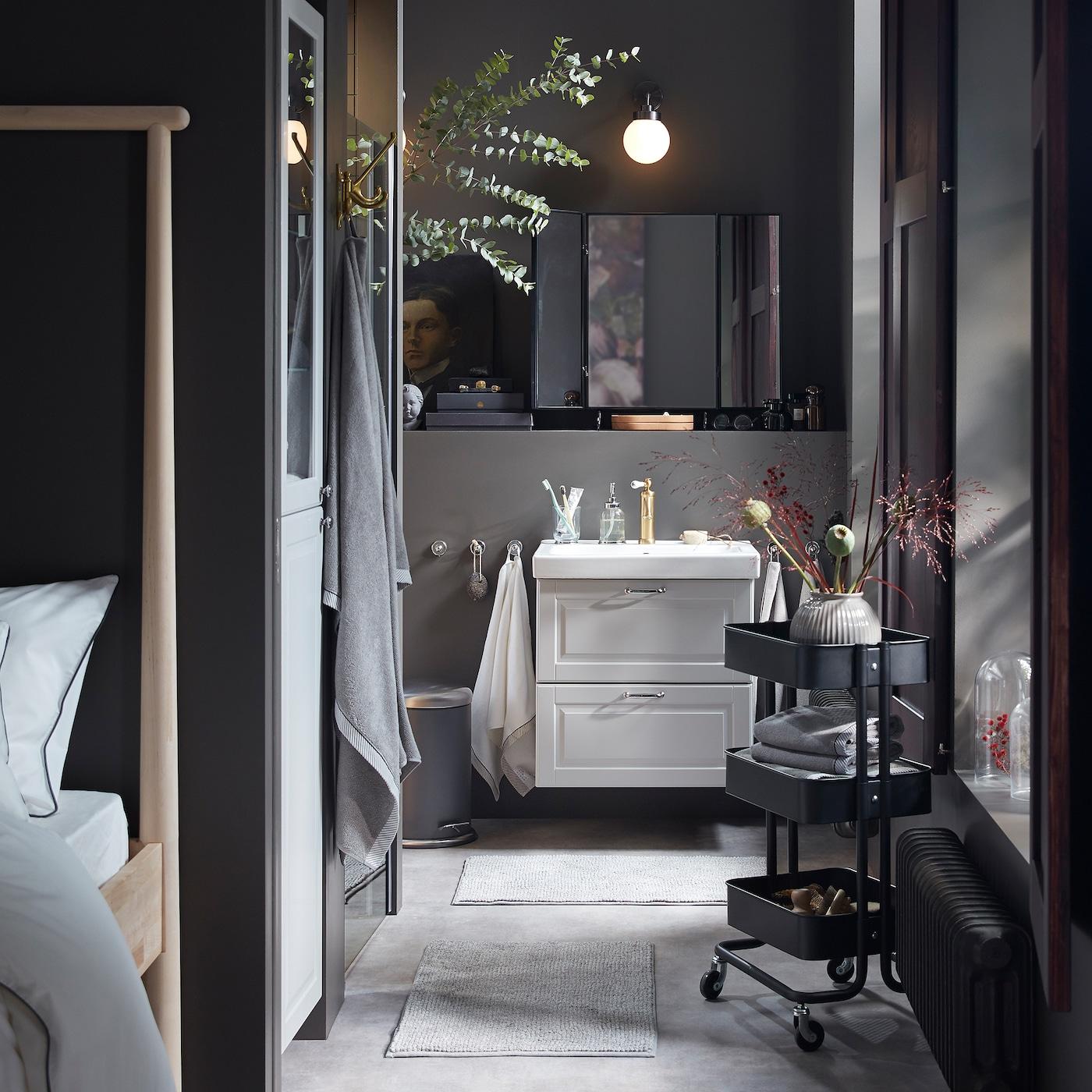 Badrum helt i grått med en kommod och högskåp i ljusgrått, svart rullvagn och många dekorativa torkade blommor.