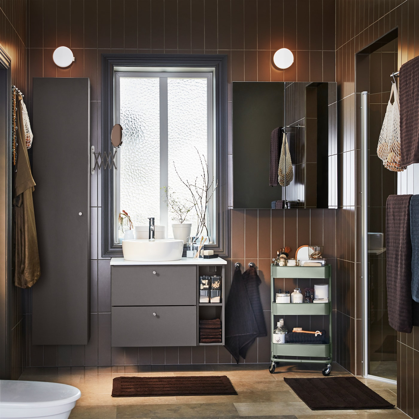 Badrum med mörkgrå badrumsmöbler, skåp med spegeldörr, grågrön rullvagn och mörkbruna badrumsmattor.