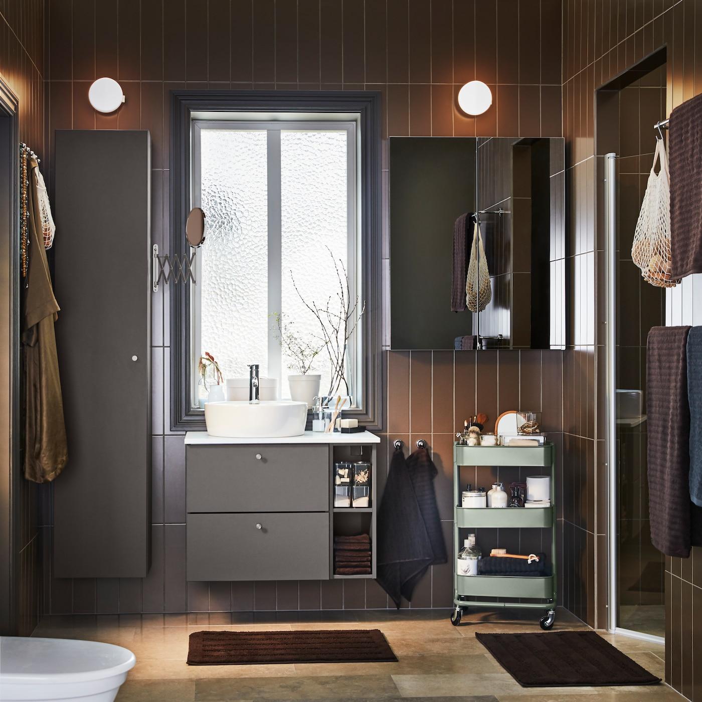 Badrum med vitt kakel och ett badkar med GATKAMOMILL turkos/vitt duschdrapperi.